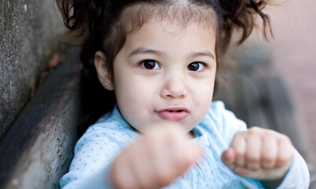 A cute toddler girl with clenched fists