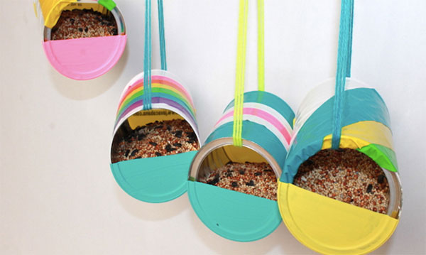 Four recycled can bird feeders hanging in front of a white background