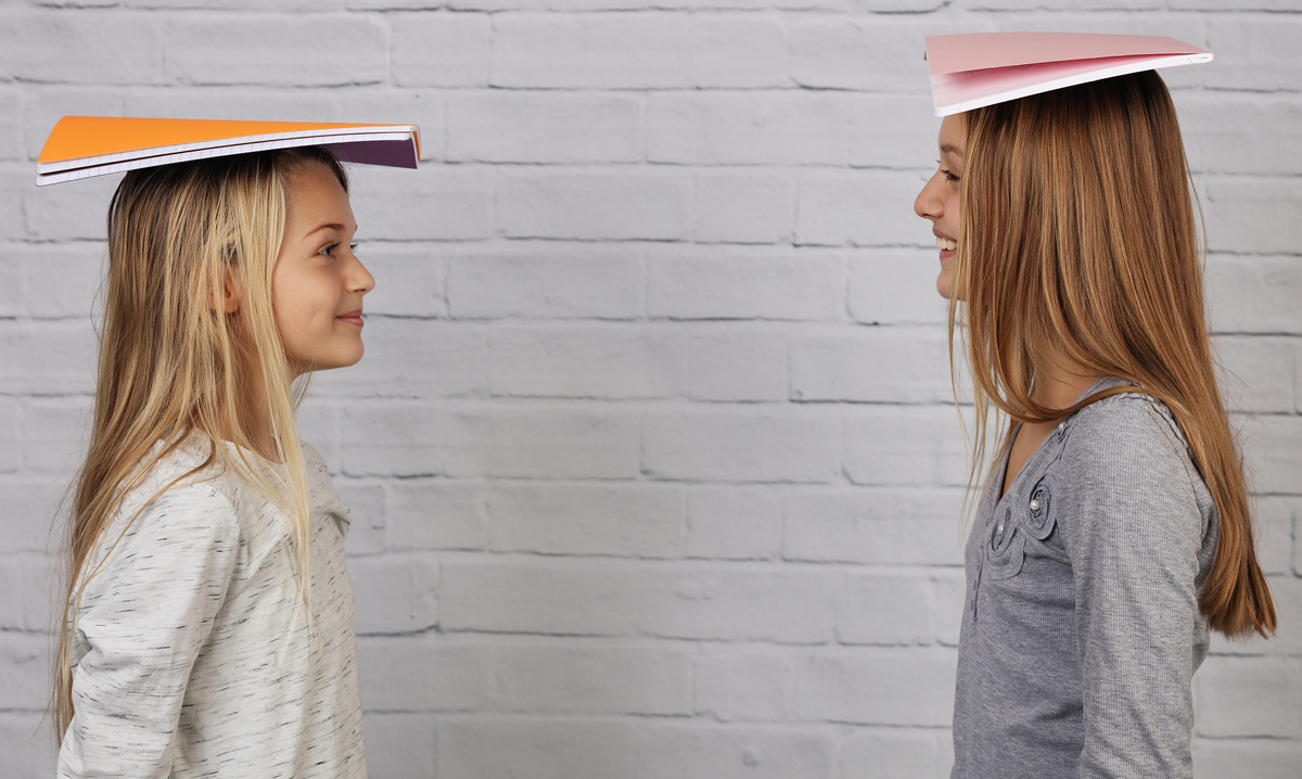 Two tween girls with notebooks balanced on their heads