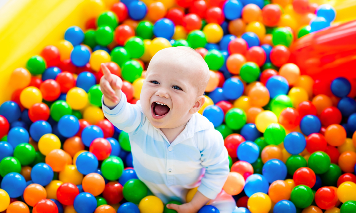 Baby laughing in a ball pit