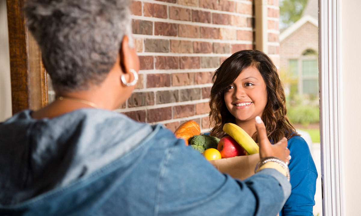 A helper brings produce groceries to an older woman's home