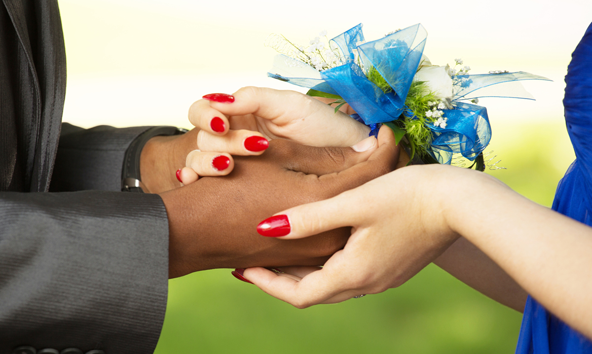 Two people holding hands. One is wearing a blue corsage