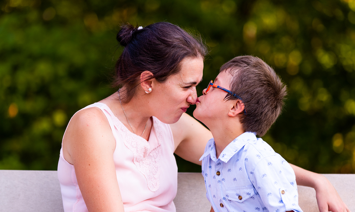 A boy with red glasses kisses mom's nose on a bench