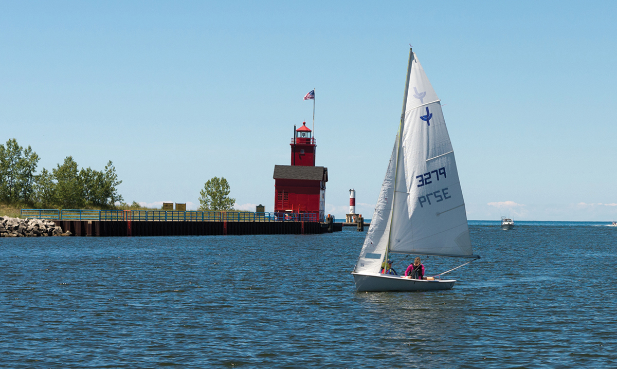 A sailboat goes past a red lighthouse on Lake Michigan