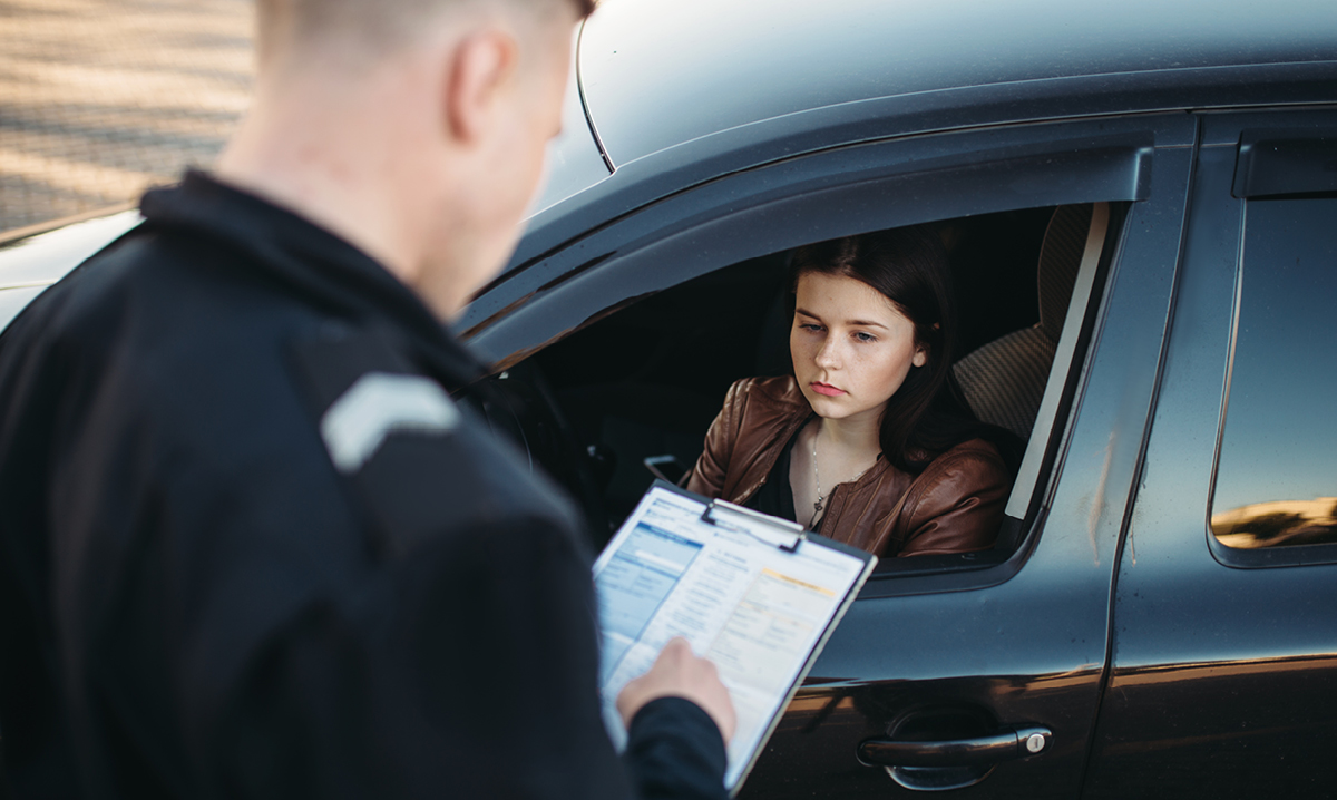 A police officer pulls over a young female teen driver