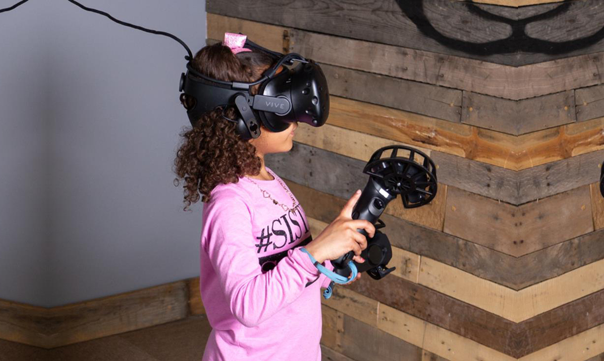 Little girl playing a game at The Sandbox Virtual Reality Arcade in Flint