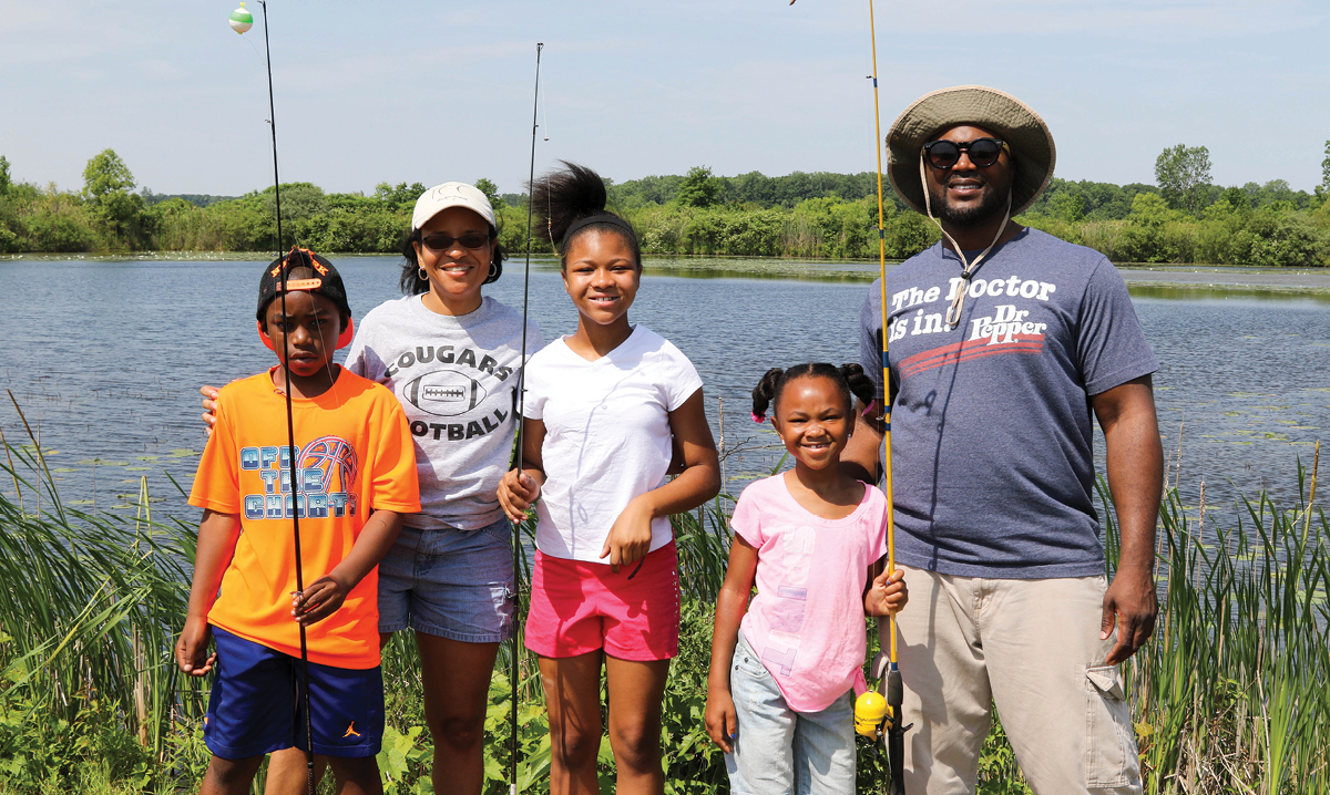 A black family of five with fishing rods near a marsh in summer