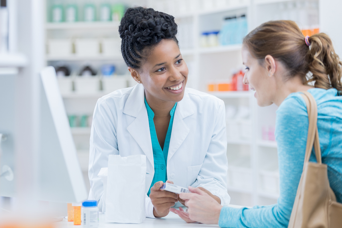 A pharmacist offers advice to a woman with a purse