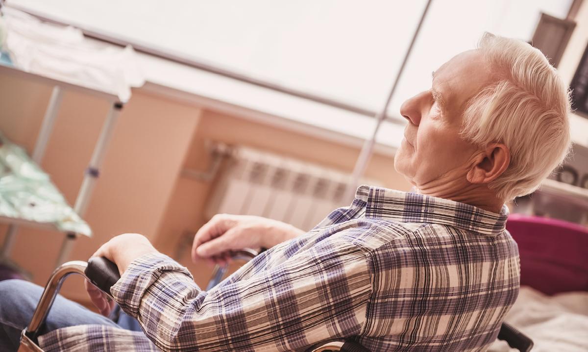 Elderly man in a wheelchair in a nursing home setting