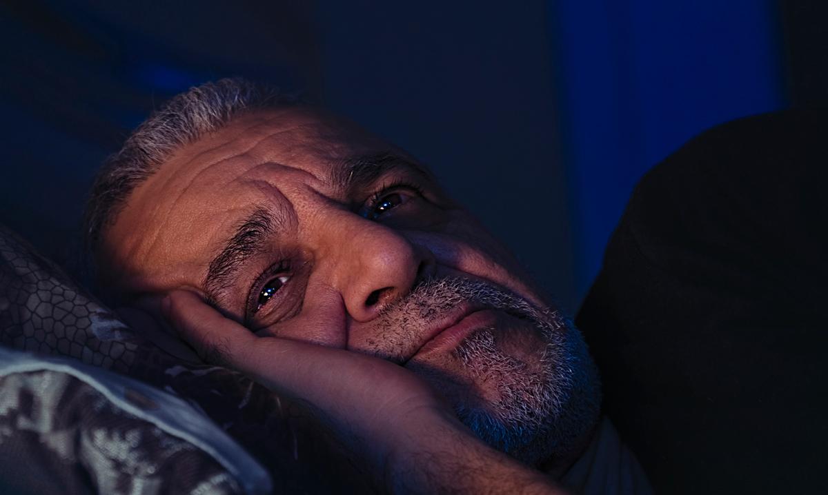 Elderly man worries on his pillow