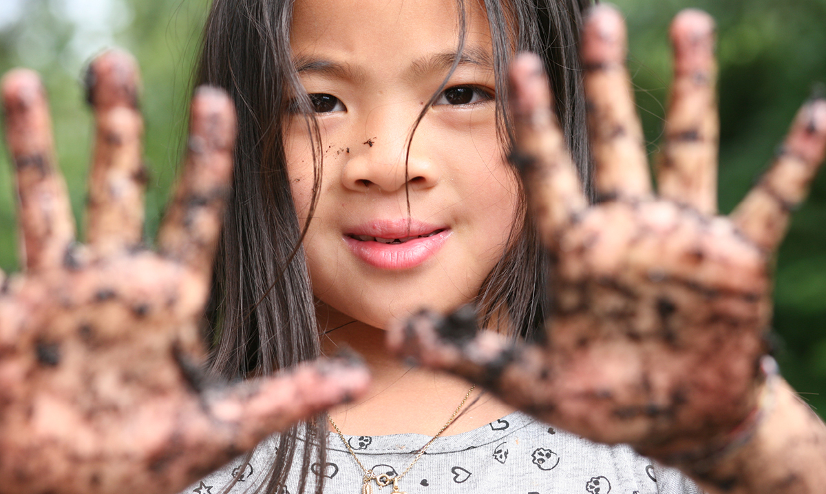 Little girl shows off dirty hands