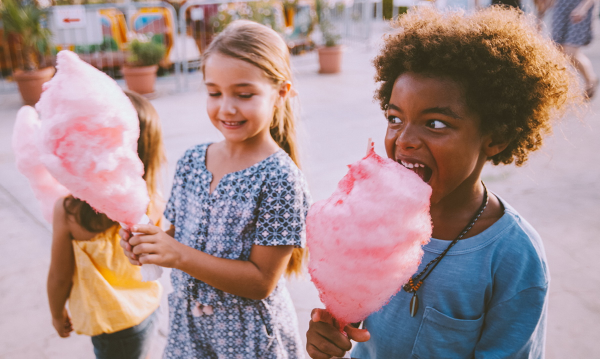 Two girls eating pink cotton candy at a fair