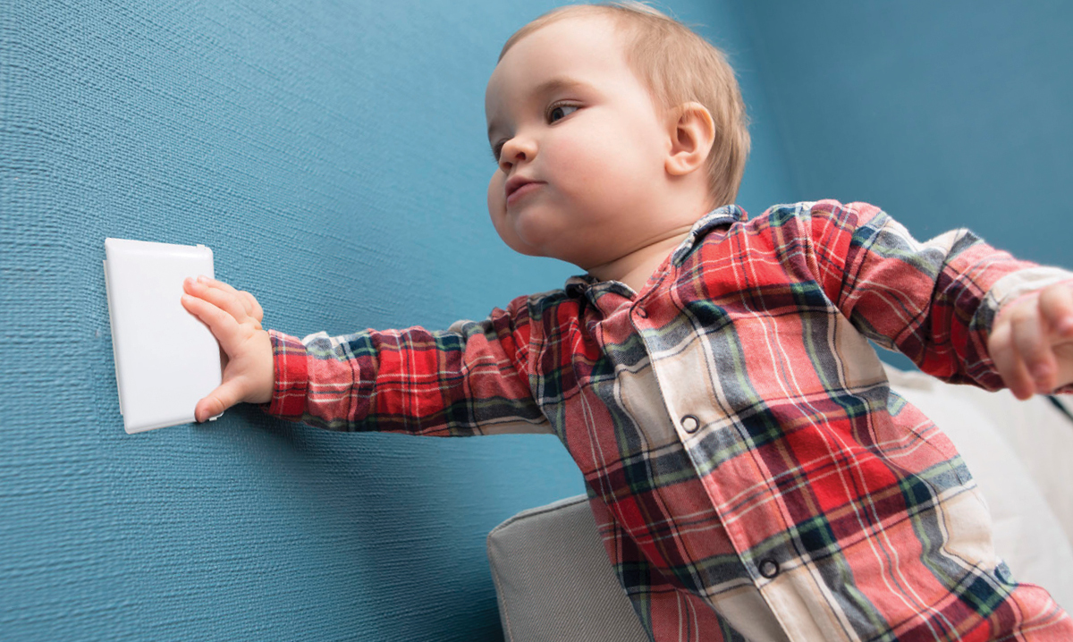 Baby in red plaid touching an outlet cover