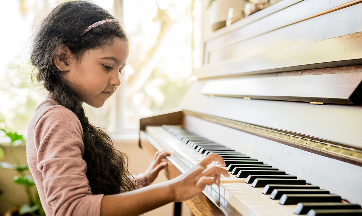 Young girl with long hair playing the piano