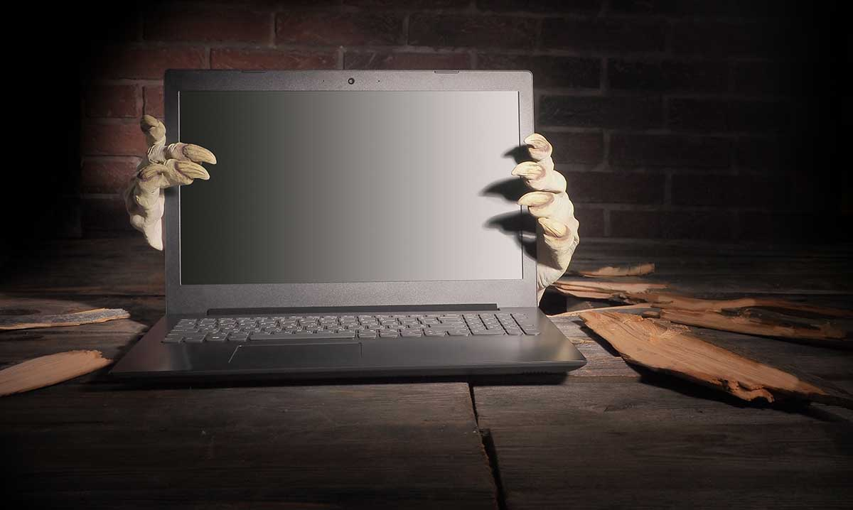 Zombie hands gripping a laptop