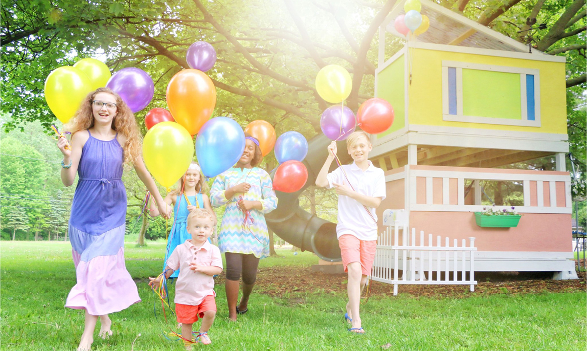 Children running with balloons in front of Up movie treehouse in Livonia, Michigan