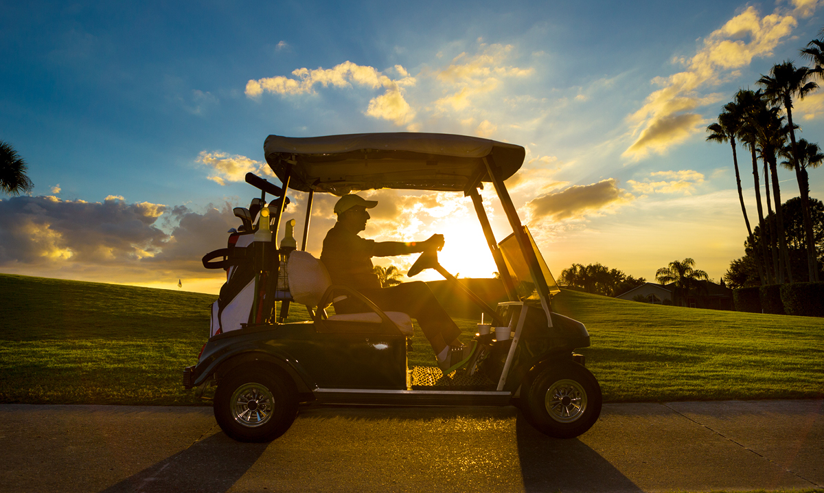 Senior man driving a golf cart in a tropic location