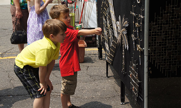 Two children looking at artwork at The Art of Fire in downtown Royal Oak