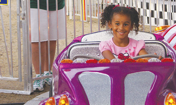 Little girl riding in a fair ride