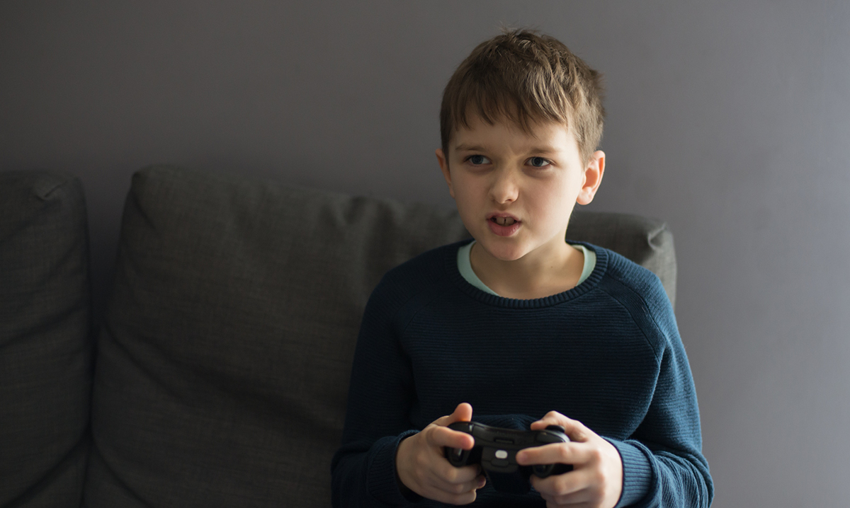 Young boy intensely playing a video game