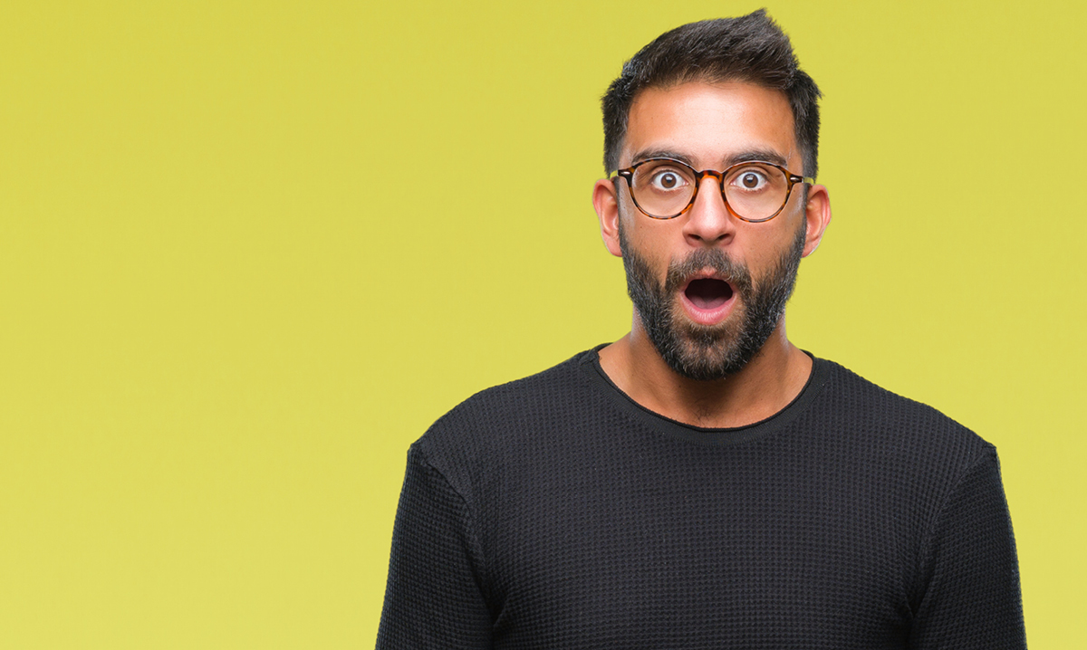 A dumbfounded young man in glasses on a yellow background