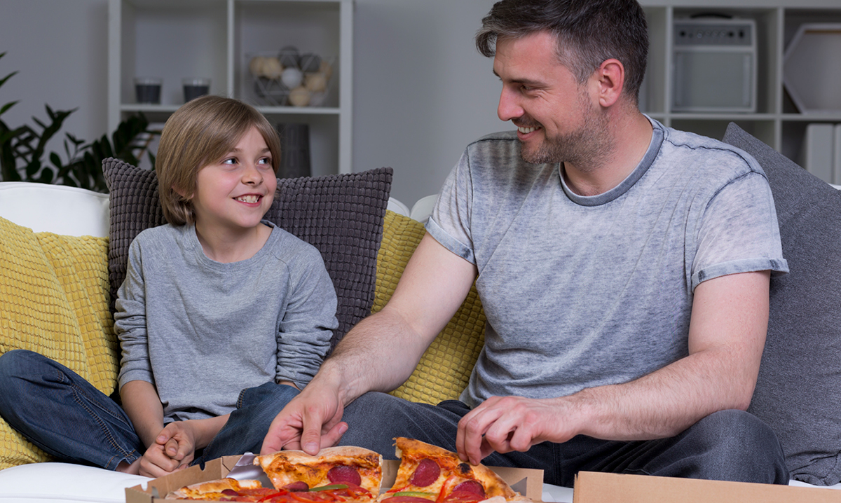 A dad shares pizza with his son
