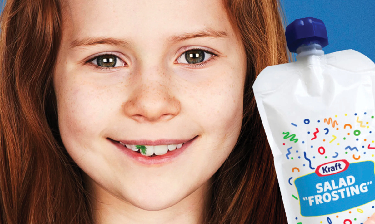 Girl with lettuce stuck in teeth next to package of new salad frosting