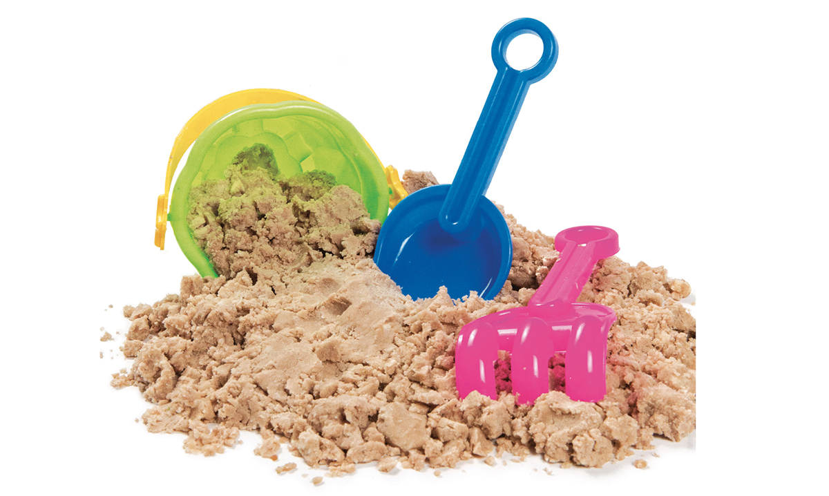 A bucket and shovels in a pile of sand
