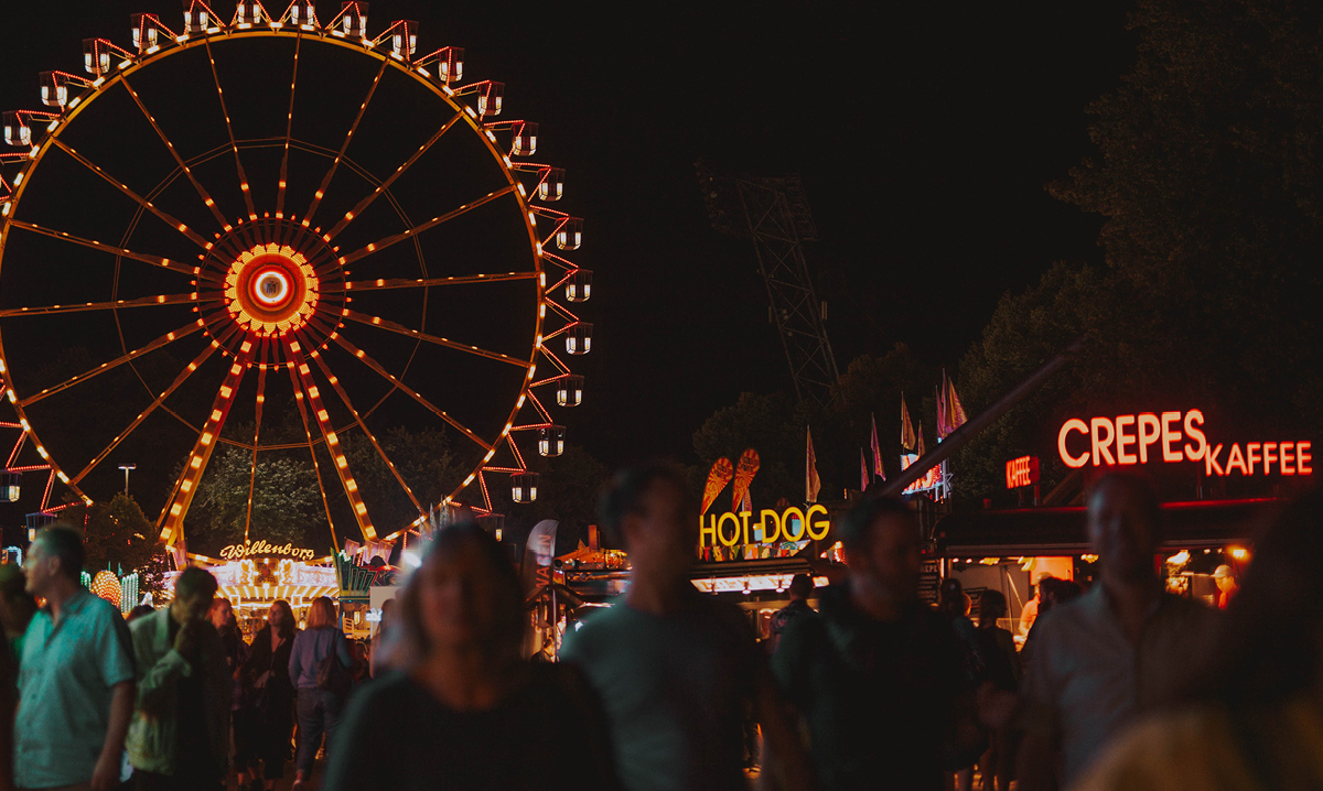 The ferris wheel at a carnival lit up against the dark sky
