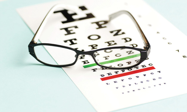 Pair of glasses on top of an eye exam chart on a light blue background
