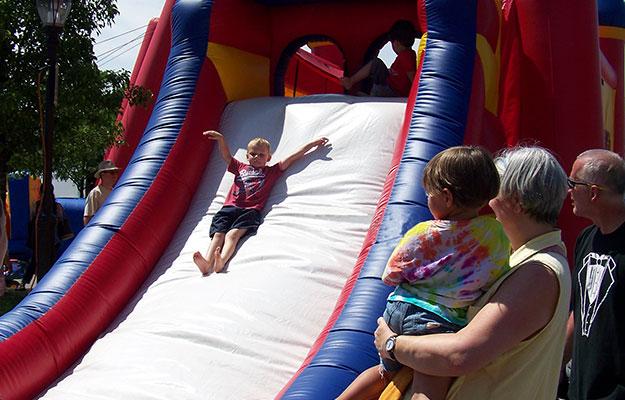 Kid sliding down inflatable slide at the Farmington Founders Festival