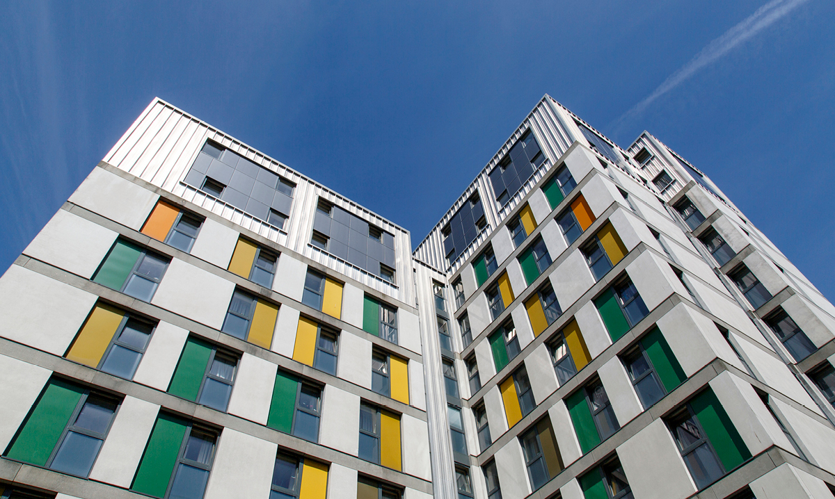 A college dorm with yellow and green accents against a blue sky