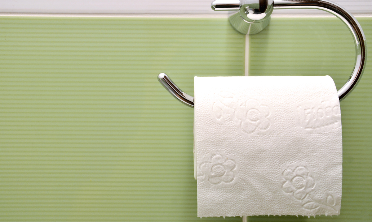 Toilet paper against a green tile wall