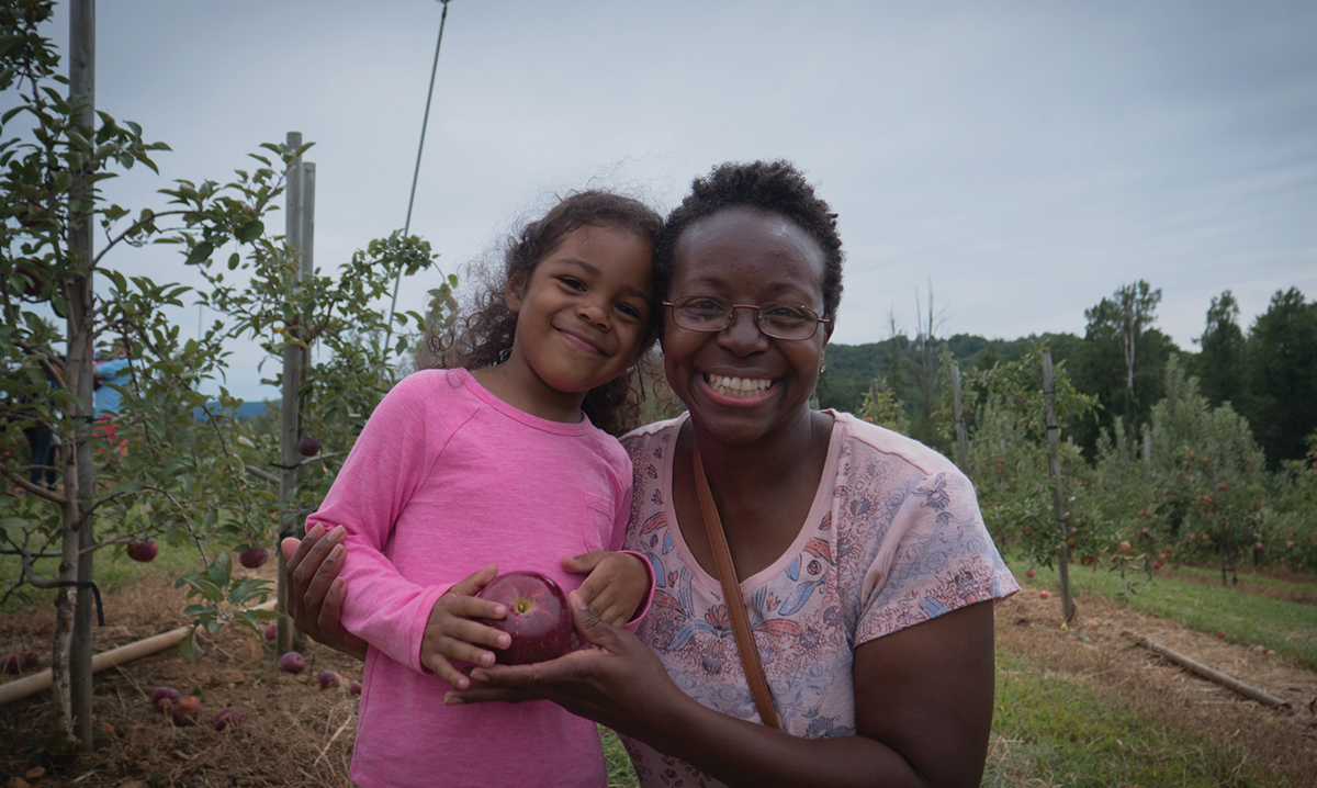 Woman and little girl in apple orchard