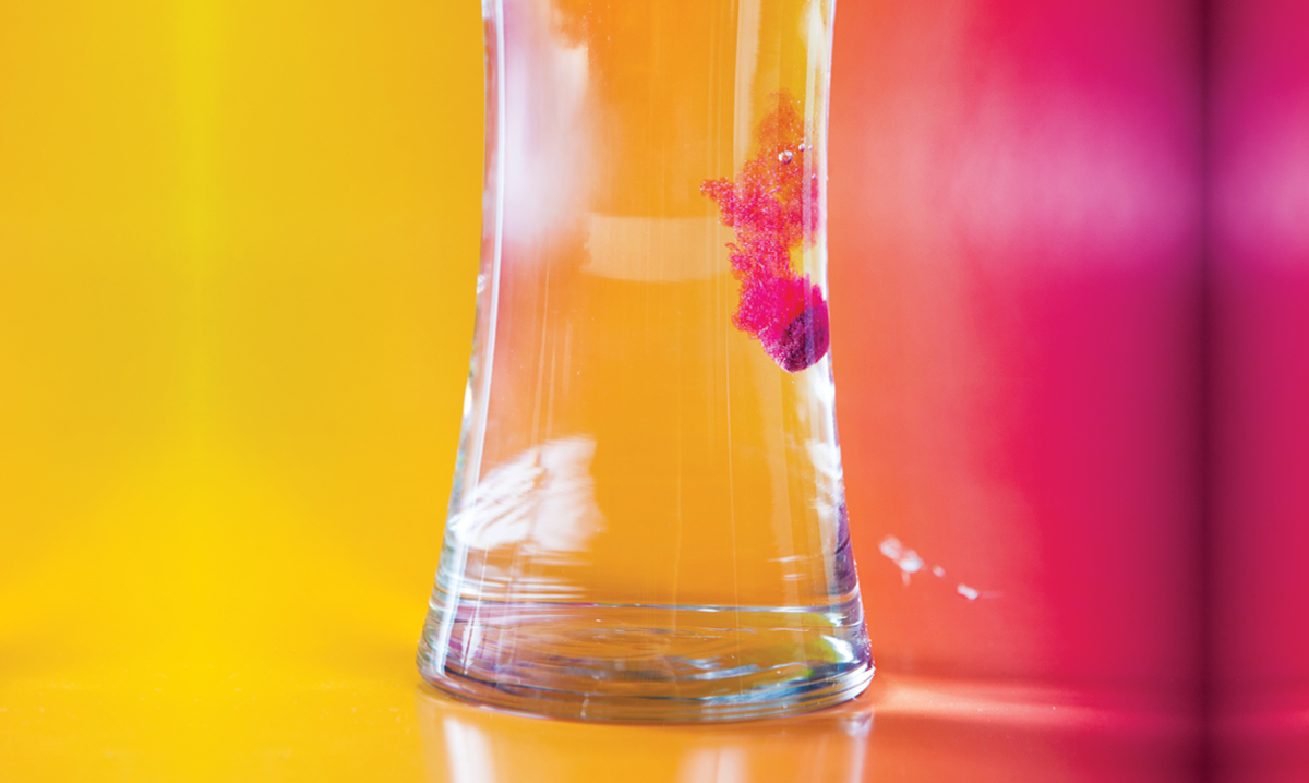 Glass of water on a yellow and pink background with a Crayola Color Bath Drop fizzing in it