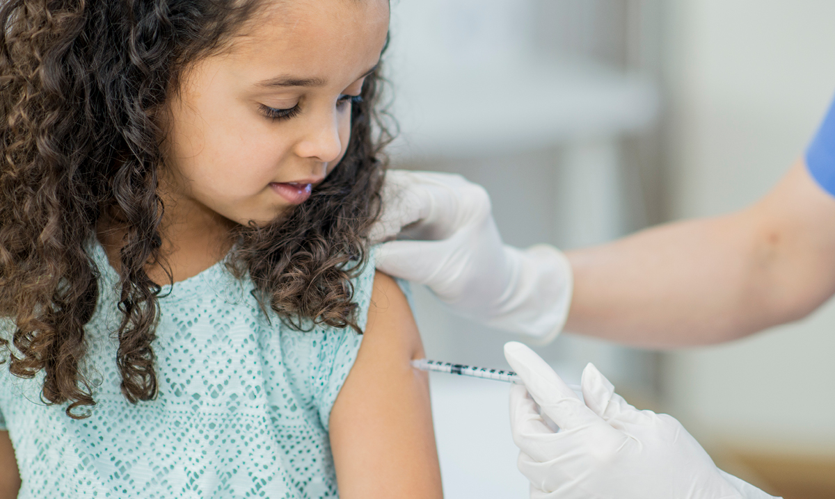 Child receiving a vaccination in her arm.