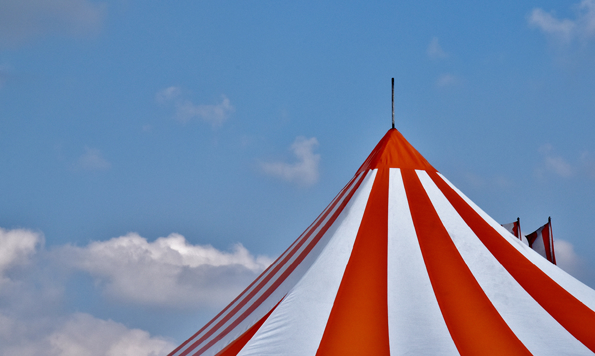 Top of a red and white carnival tent against a blue sky