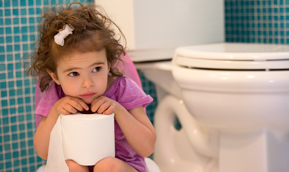 Little girl on training potty holding toilet paper in front of a toilet