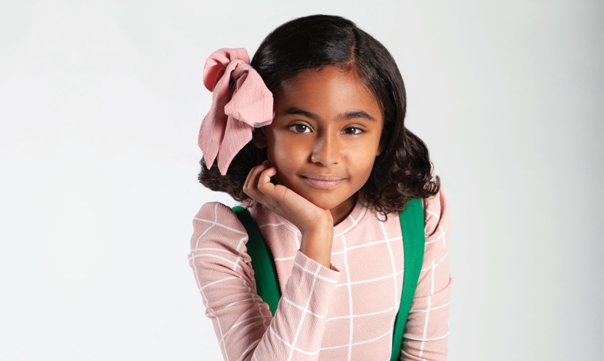Girl wearing pink shirt and a pink bow with a green backpack puts head in hand and looks into camera