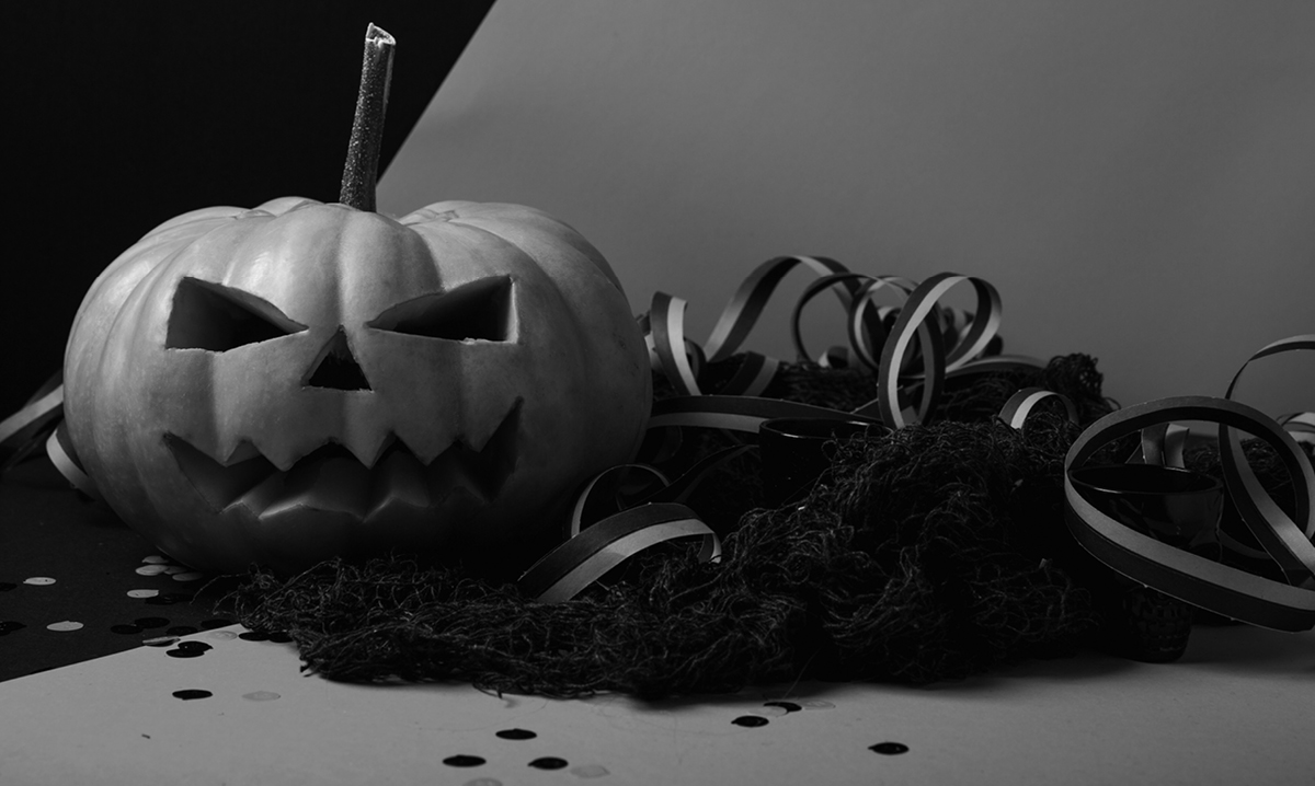 black and white photo of a pumpkin surrounded by ribbon