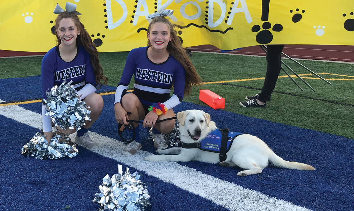 Dakota the therapy dog sitting with two cheerleaders