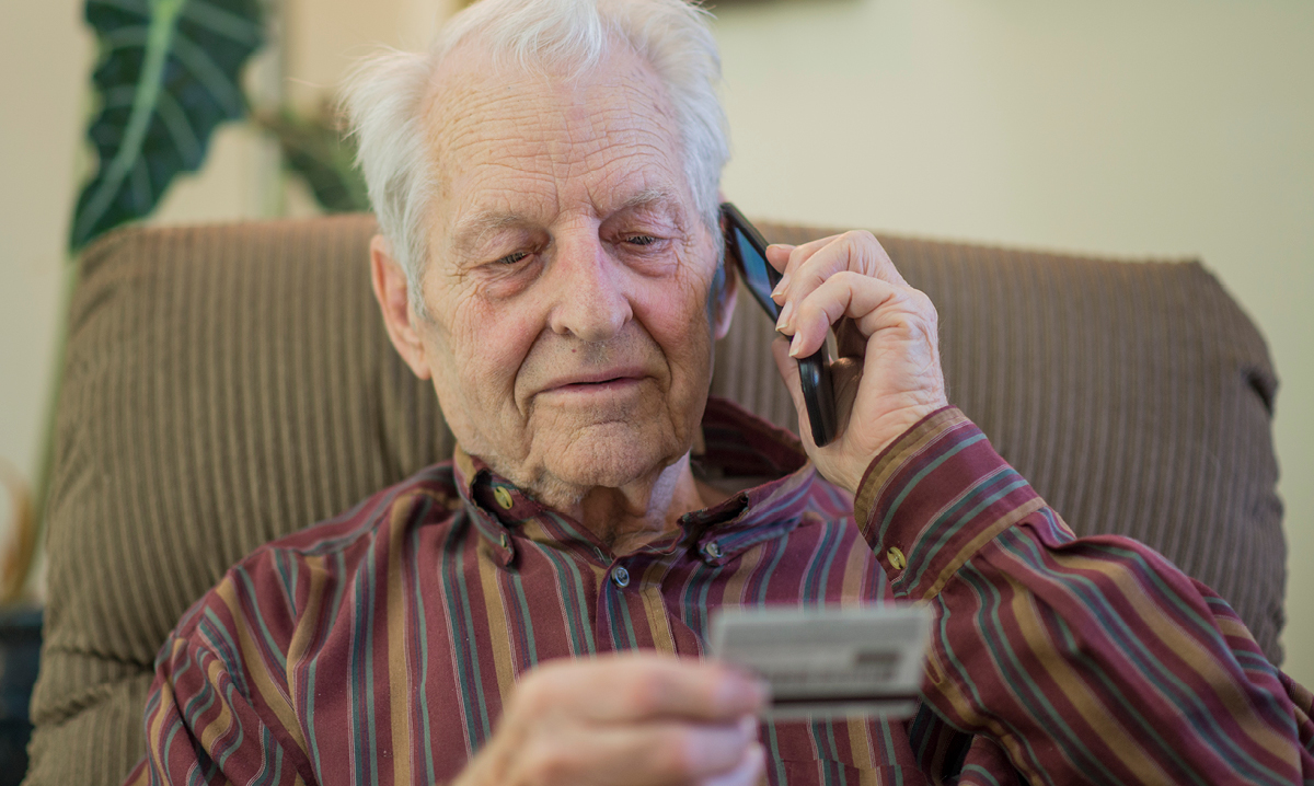Old man on phone looking at credit card