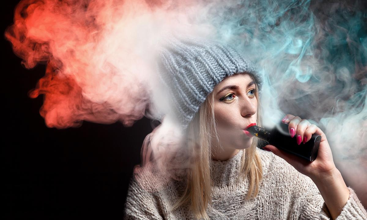 Teen in grey hat smoking e-cigs
