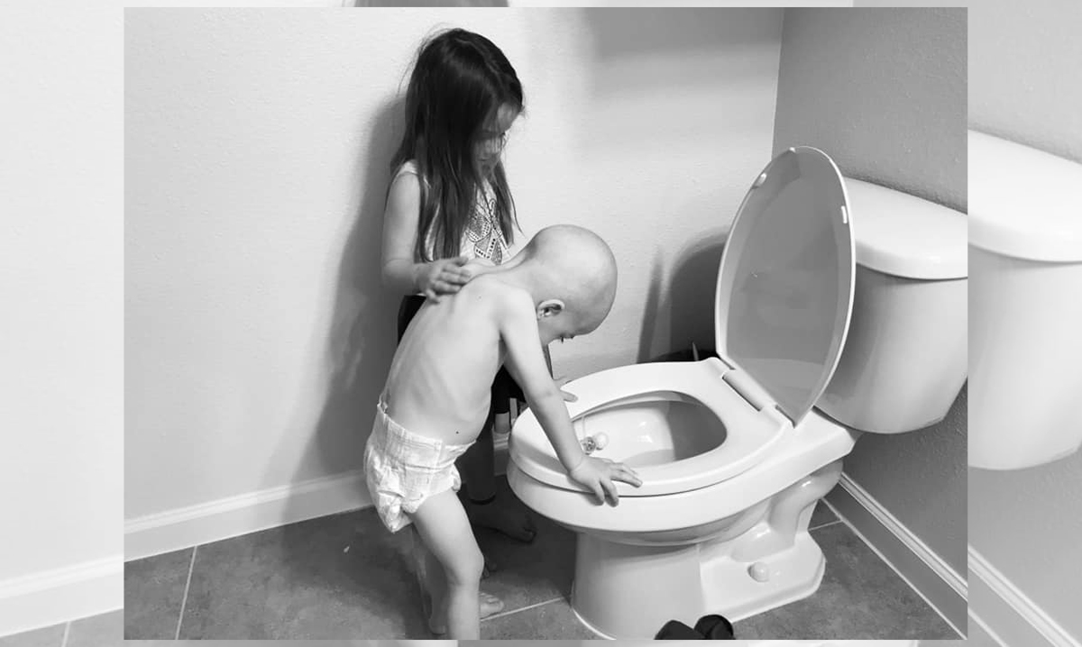 Beckett Burge leans over the toilet while his sister comforts him