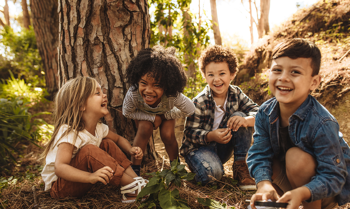 Four kids playing in front of a tree