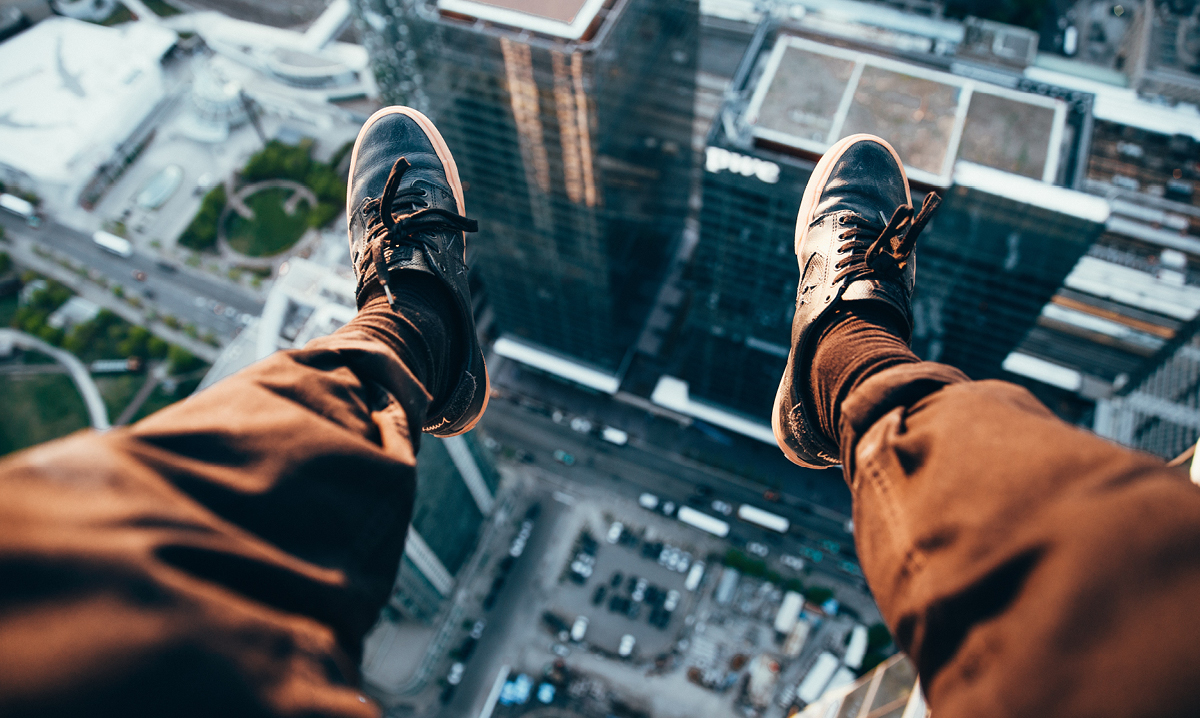 Feet dangling off a building above a city