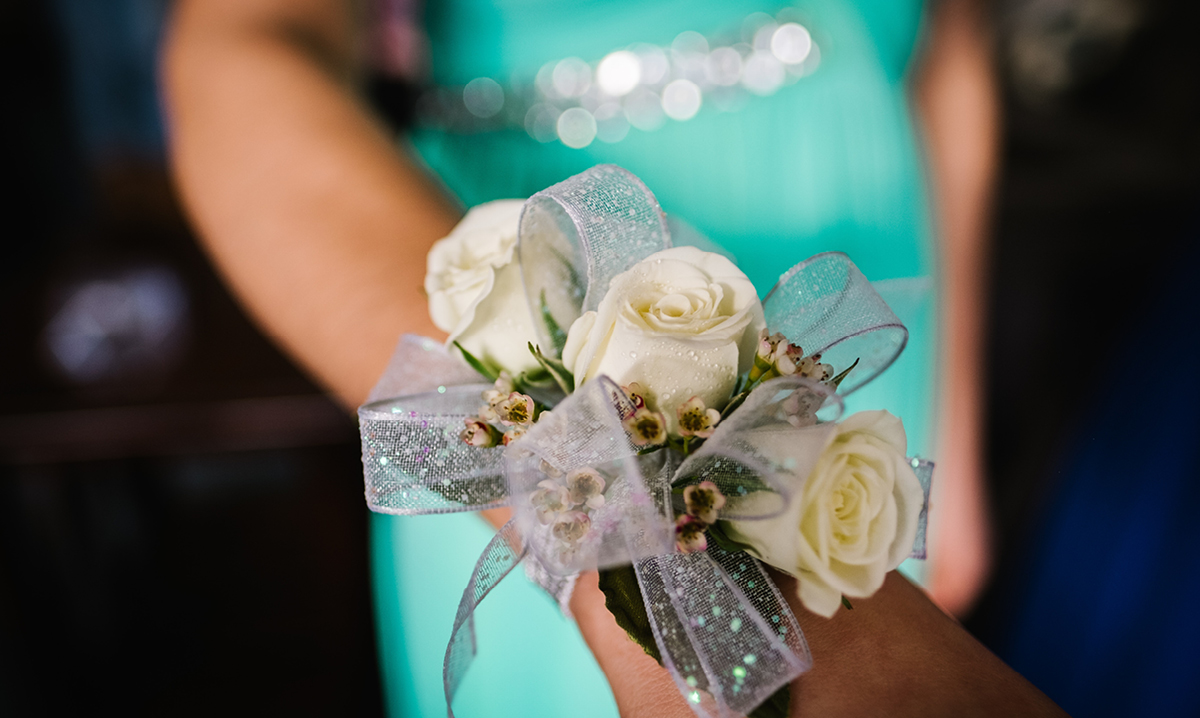 flowers on a wrist with a teal dress in the background