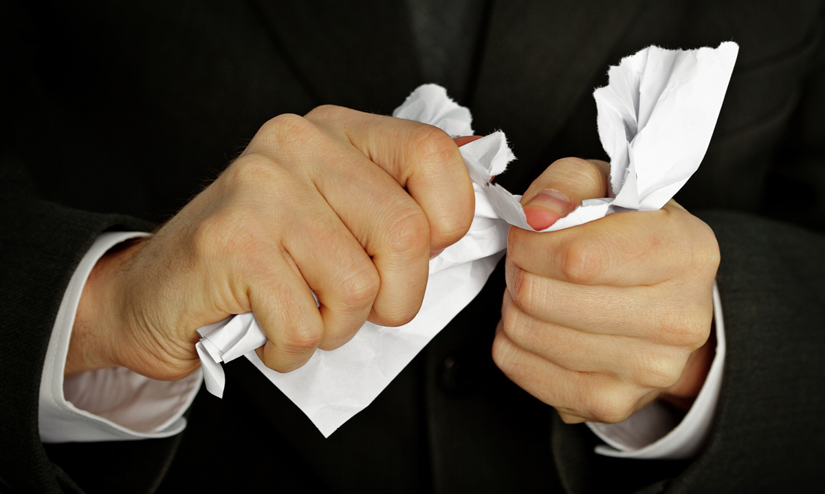 Man hands tearing up paper