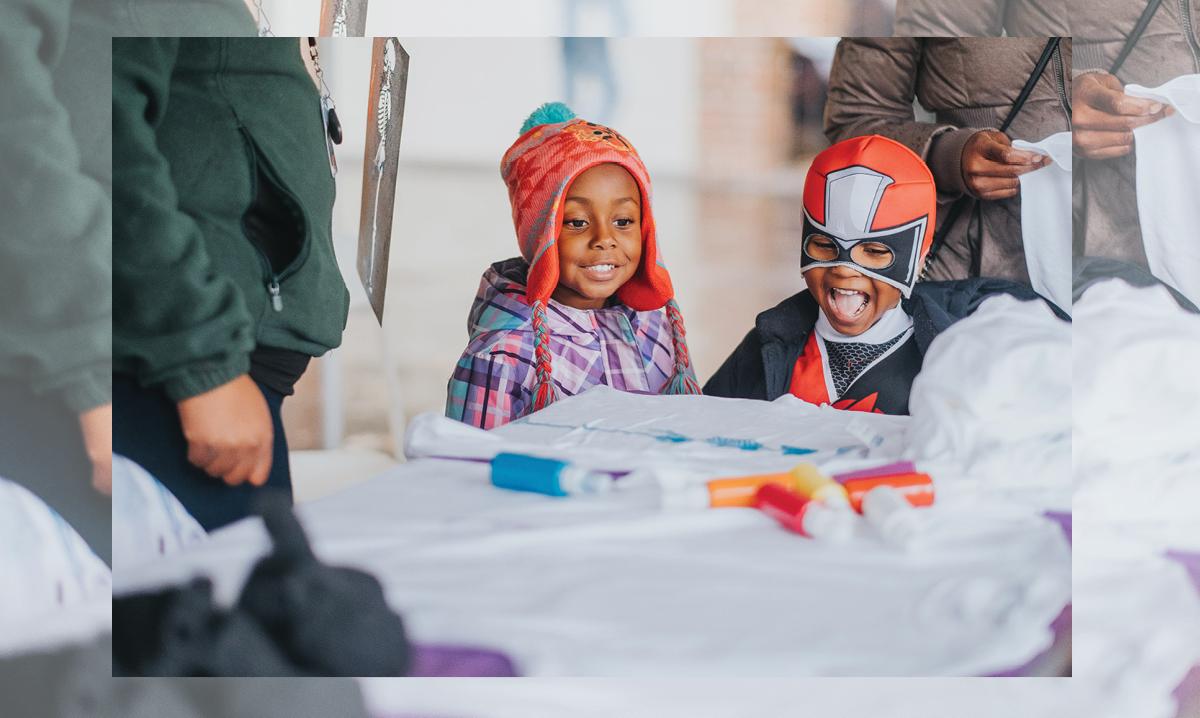 Two children making Halloween crafts in Flint