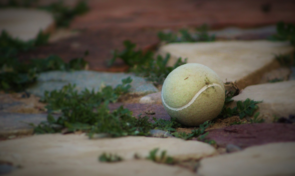 A dirty tennis ball on cement